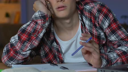 can sıkıntısı : School pupil talking phone while doing homework, feeling bored, studying break