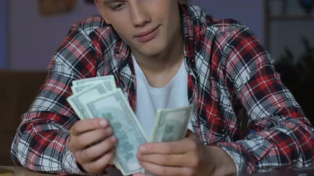 odpowiedzialność : Handsome teenager counting dollar bills, sitting at table, dreaming purchase Wideo