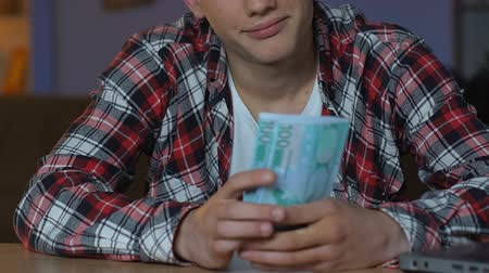 školák : Rich young man counting euro banknotes, sitting home table, investment plan