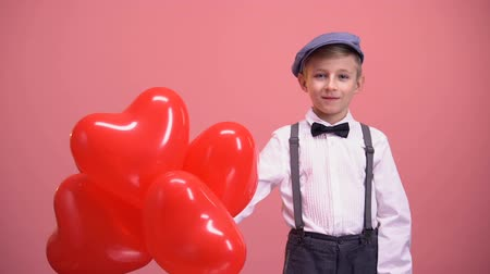 gratulací : Smiling kid in vintage clothes presenting heart-shaped balloons, Valentines day