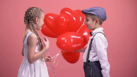 dávat : Boy in love giving cute girl heart-shaped balloons, Valentines day surprise