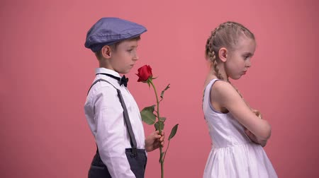 apologize : Gentleman boy with red rose apologizing to offended girlfriend, first love Stock Footage