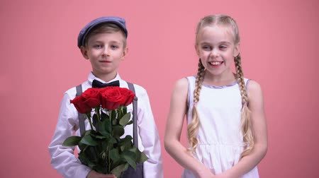 shy girl : Smiling girl and her little boyfriend holding red flowers, looking to camera