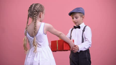 shy girl : Little girl in white dress giving wrapped present to boyfriend, Valentines day