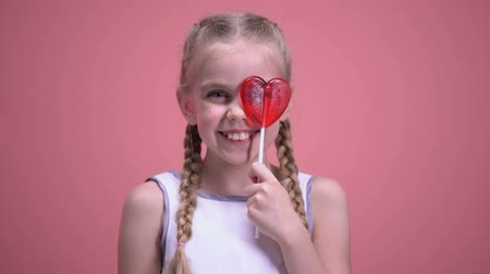 фасонный : Smiling girl with braids having fun, closing eye with heart-shaped lollipop