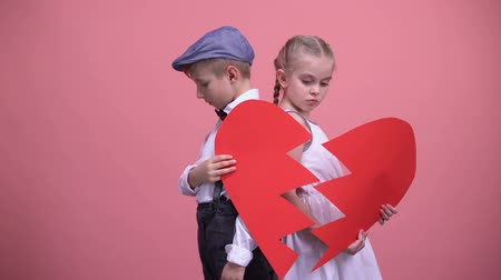 jealous : Sad little couple holding broken pieces of red heart, quarrelling, brake up Stock Footage