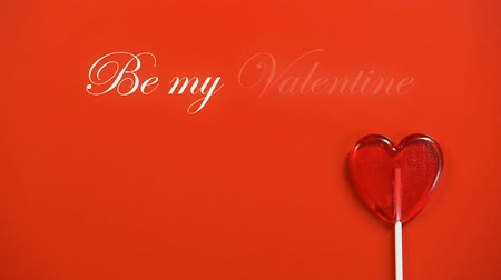 lolly : Be my Valentine phrase and heart-shaped lollipop isolated on red background Stockvideo