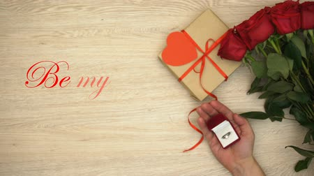 karát : Be my Valentine phrase and male hand with engagement ring near gift and flowers Stock mozgókép