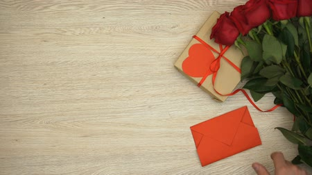 конверт : Hand putting red envelope on wooden table near bunch of roses and gift box, love