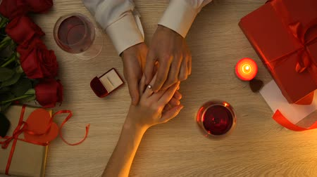 propor : Man wearing engagement ring on womans hand during romantic date on Valentine Day
