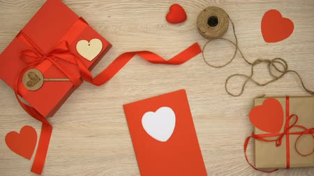 чувствовать : Hand made Valentines greeting card on wooden background near craft gift boxes Стоковые видеозаписи