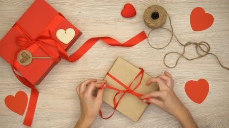 anniversary congratulations : Person packing craft Valentines gift box on wooden background, preparation Stock Footage
