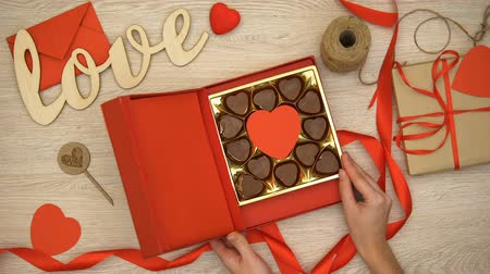 сладость : Lady opening Valentines giftbox with heart-shaped chocolate candies, aphrodisiac