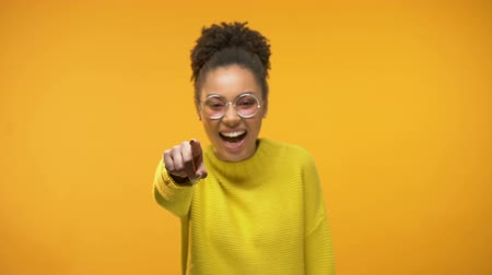 isteyen : Smiling black lady pointing finger at camera, choosing winner, yellow background