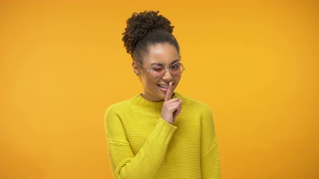 taboo : Afro-American lady in eyeglasses showing silence gesture and wrinkling, flirting Stock Footage