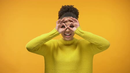 binocular : Smiling black woman making faces, having fun, isolated on yellow background Stock Footage