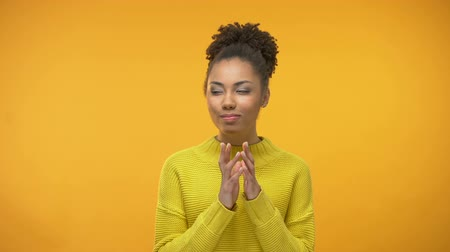 tricky : Sly Afro-American girl having idea, tricky plan, isolated on yellow background