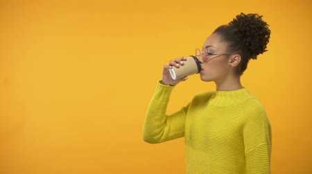 koffie verkeerd : Black girl in eyeglasses drinking disgusting coffee to-go, off-flavor taste Stockvideo