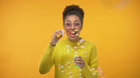 sabão : Excited African-American girl blowing soap bubbles, childish mood, happiness