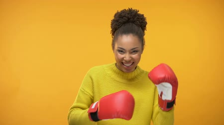 utánzás : Smiling Afro-American girl in boxing gloves imitating fight, having fun, victory