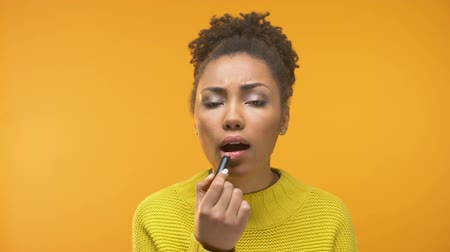 outlook : Afro-American young woman applying lipstick, unsatisfied with matched color