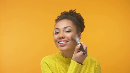 косметика : Happy black woman applying blush, young lady preparing for date, close-up Стоковые видеозаписи