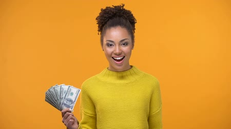 concordar : Beautiful black lady showing bunch of dollars and ok gesture, cash-back services