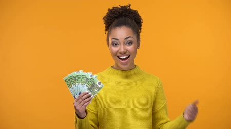 euro banknotes : Smiling African-American lady showing bunch of euros to camera, high-paid job