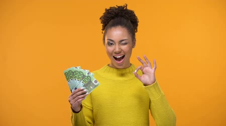 okey : Pretty black lady showing bunch of euros and ok gesture, cash-back services