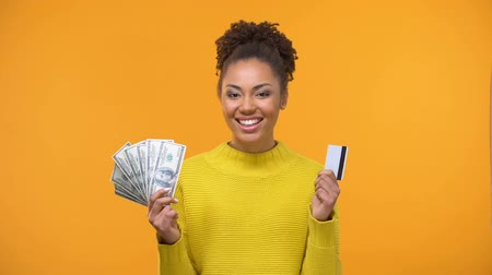 számlák : Attractive black lady holding bunch of dollars and credit card, online payment