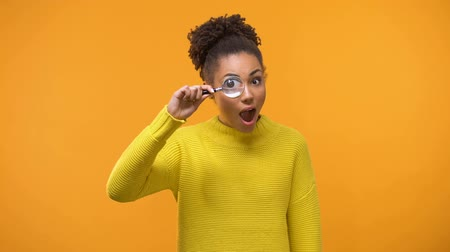 suspecting : Curious african american woman looking through magnifying glass, having fun