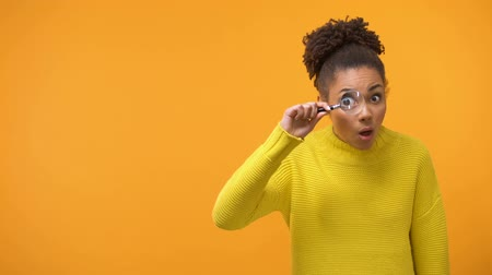 opsporing : Teenage girl looking in magnifying glass, shocked and surprised by information Stockvideo