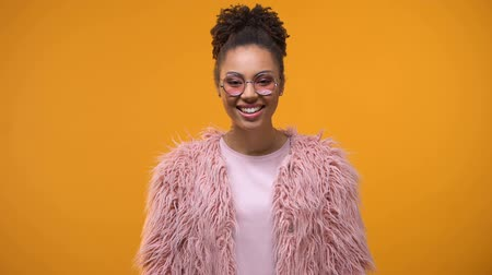 afro amerikan : Attractive and stylish girl smiling, standing on yellow background, good mood Stok Video