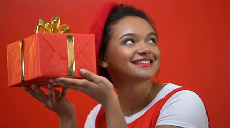 szál : African american woman shaking giftbox trying to guess what is inside, present Stock mozgókép
