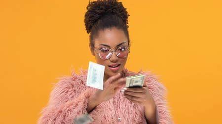 piyango : Young black female throwing around dollar bills and smiling into camera, success Stok Video