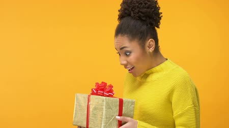 восхищенный : Delighted african female looking gift box in hand, receiving present happiness Стоковые видеозаписи