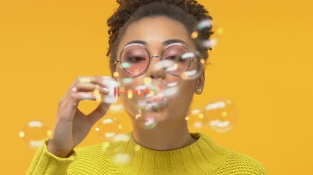 fiatalos : Carefree female teenager blowing soap bubbles and smiling into camera, childhood