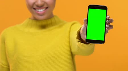 mobilità : Smiling young lady in yellow sweater showing smartphone with green screen, app