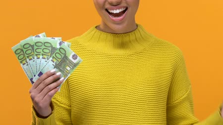 earnings : Happy black female pointing at euro banknotes in hand, financial success, salary