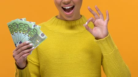 легкий : Young female holding euro bills and showing ok sign, exchange rate, wealth Стоковые видеозаписи