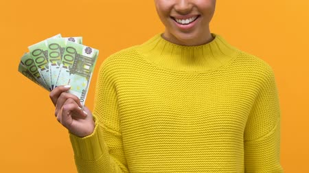 награда : Smiling young female holding euro banknotes and credit card in hands, payment Стоковые видеозаписи