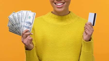 prémie : African woman holding dollar banknotes and credit card in hands, bank account