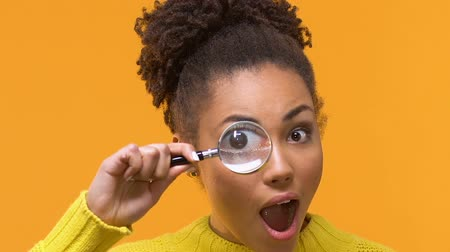 pertavsız : Playful young woman looking at camera through magnifying glass, curiosity search Stok Video