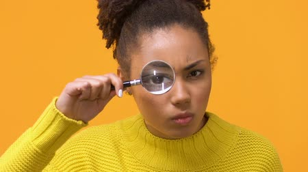 pertavsız : Serious african woman looking through magnifying glass, female detective, search Stok Video