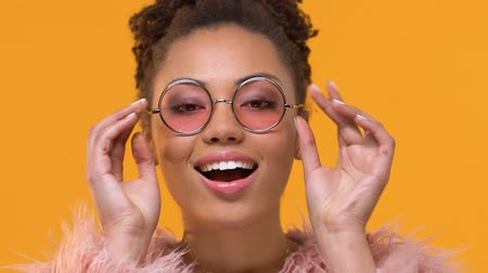 nőiesség : Joyful afro-american stylist putting on fashionable eyeglasses yellow background