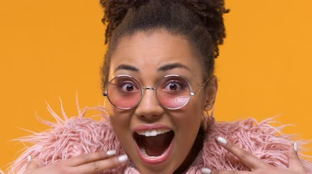 vay : Amazed stylish female in pink eyeglasses looking camera, excitement expression