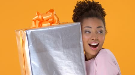 piada : Excited young lady holding huge bow present, gift delivery service, surprise Stock Footage