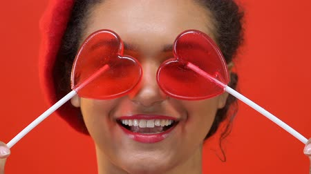 lolly : Happy female teenager in stylish red beret holding heart candy front of eyes