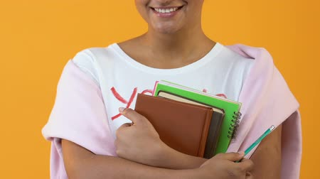 intelectual : Female student with books and pencil standing on yellow background, education Archivo de Video