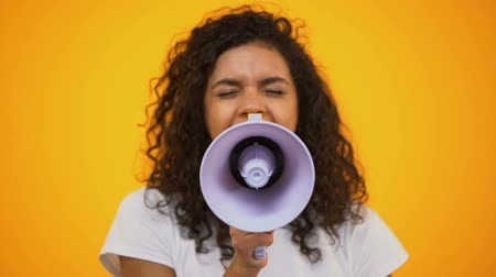 объявлять : African-American woman using megaphone for protest, public opinion, politics